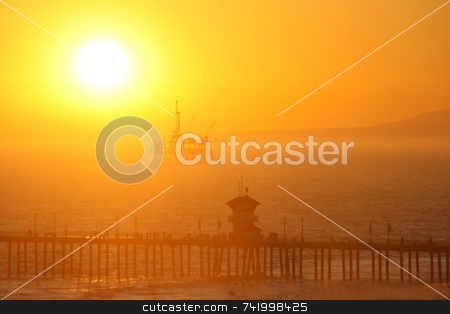 Offshore oil rig at sunset stock photo, An offshore oil rig lit from behind by the setting sun which is going down in a blaze of glory. by Mitch Aunger