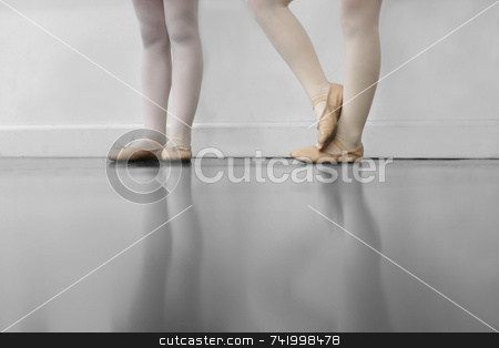 Dance Class stock photo, Young dancers are learning - they're witing to see what the instructor says to do next... low angle shot of just their feet and legs - this view has had the color removed from the floor and wall. by Mitch Aunger