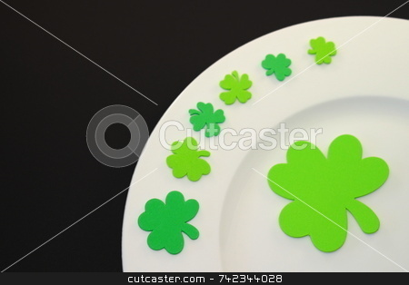 St. Patrick's Day Plate stock photo, White plate on black background with green clover leafs. by Henrik Lehnerer