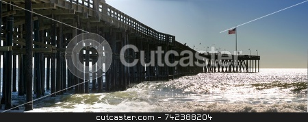 Ventura Pier stock photo, The Ventura Pier with waves and the flag at the end. by Henrik Lehnerer