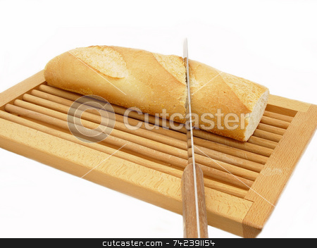 Cutting Bread stock photo, Cutting bread on a bread board by Jack Schiffer