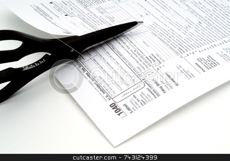 Cutting taxes stock photo, Closeup of scissors cutting a tax form by Vince Clements