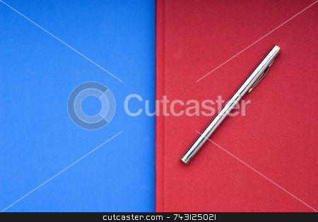 Red book on a blue background stock photo, A stricking image of a silver pen on a bright red book on a blue background by Vince Clements