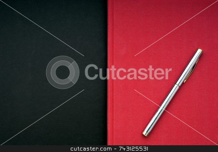 Bright red book on a black background stock photo, A stricking image of a silver pen on a bright red book on a black background by Vince Clements