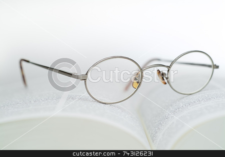 Book and reading glasses stock photo, High key closeup of reading glasses on an open book by Vince Clements