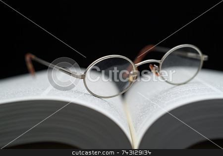Closeup of reading glasses on large book stock photo, Closeup of reading glasses on large book shallow focus by Vince Clements
