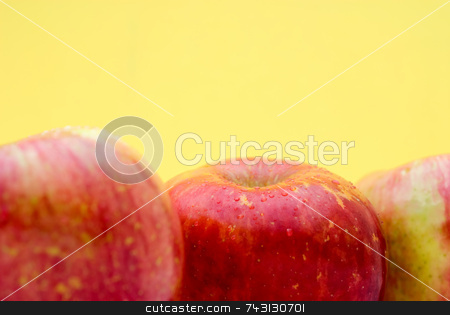 Fresh apples on bright yellow stock photo, Fresh red apples on a bright yellow background with shallow focus by Vince Clements