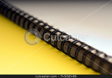 Macro of a ring bound document - on yellow stock photo, Macro of a white spiral ring bound document - on a yellow background by Vince Clements