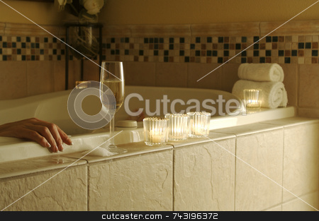 Woman In Tub stock photo, Woman relaxing in a tiled tub. Sparkling wine, candles and towels adorn the scene. by Andy Dean