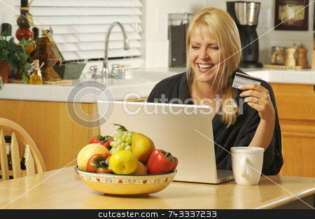 Woman Using Laptop for E-commerce stock photo, Woman holding credit card in her kitchen Using her Laptop for Ecommerce. by Andy Dean