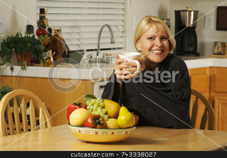 Woman with Cup of Coffee in Kitchen Smiling stock photo, Beautiful young successful woman, enjoying a cup of coffee in her home. by Andy Dean