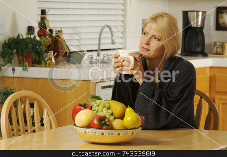 Woman in Kitchen with Cup of Coffee stock photo, Beautiful young, successful woman pondering things over a cup of coffee in her home. by Andy Dean