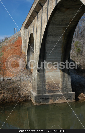 Under the bridge stock photo, The underside of a railroad bridge over a small creek by Tim Markley