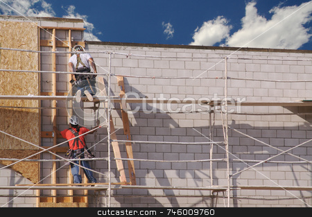 Carpenters Working Diligently stock photo, Carpenters working diligently along scaffolding one summer morning. by Andy Dean