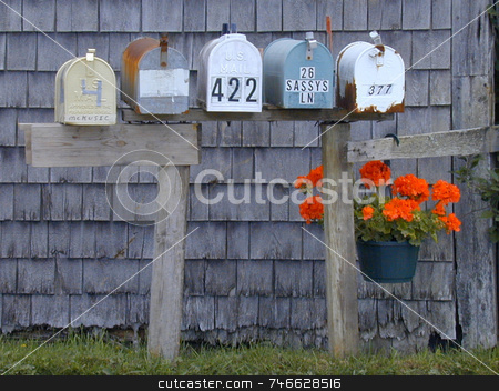 Mailboxes and Geranium stock photo, A row of mailboxes along a rural road, decorated with a hanging geranium by Tom and Beth Pulsipher