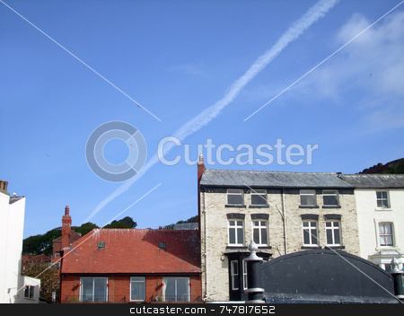 Airplane vapour trails in blue sky stock photo, Airplane vapour trails in blue sky over english seaside architecture. by Martin Crowdy
