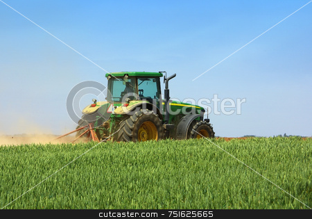 Green tractor  in the field. stock photo, Green tractor working in the field. by Inacio Pires