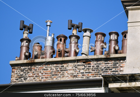 Chimneys stock photo, Line of old chimneys on a building rooftop agaist a blue sky by Massimiliano Leban