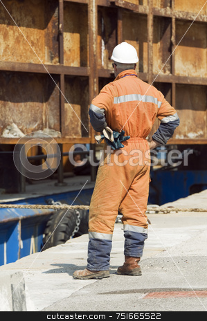 Worker stock photo, Workman with safety helmet controlling the laying of a metallic structure by Massimiliano Leban