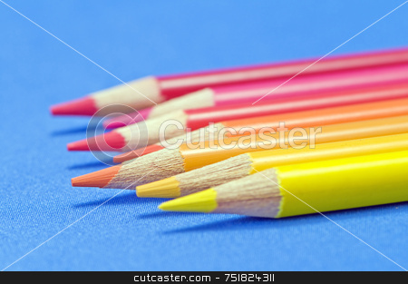 Coloured pencils stock photo, Yellow to red pencils macro on blue by Massimiliano Leban