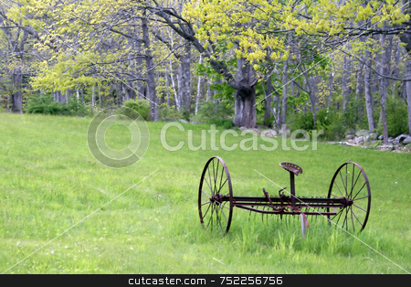 Old Hay Rake in Spring  stock photo, In a rural field, an antique hay rake lies rusting on a beautiful Spring day by Tom and Beth Pulsipher