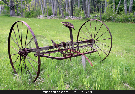 Antique Hay Rake, Rusted stock photo, An old hay rake, rusted, lying in a green field by Tom and Beth Pulsipher
