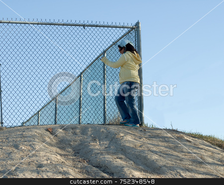 Escape stock photo, A young girl standing at the top of a security hill near the fence, trying to escape by Richard Nelson