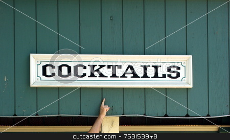 Hand Pointing To A Cocktail Sign stock photo, A cocktail sign on an old wooden building with a finger pointing to it. by Lynn Bendickson