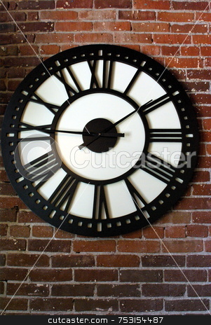 Roman Numeral Clock On A Brick Wall stock photo, A large outdoor roman numeral clock on a brick wall. by Lynn Bendickson