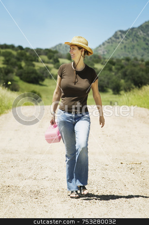 Woman on a Country Road stock photo, Woman in a cowboy hat and casual clothes walking down a country road by Scott Griessel
