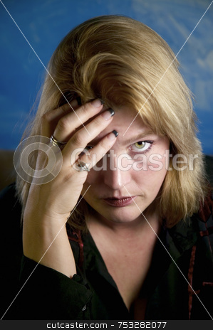 Blonde Woman Touching Forehead stock photo, Close up of blonde woman in a studio setting touching her temple. by Scott Griessel