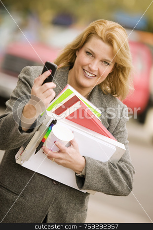 Woman with many books on a sidewalk stock photo, Pretty smiling woman with a cell phone and books walking in an urban setting by Scott Griessel