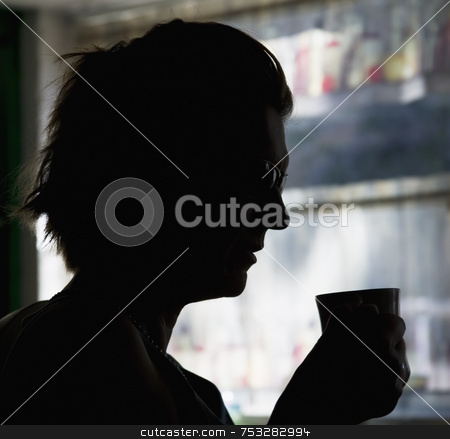 Coffee Silhouette stock photo, A woman  in silhouette drinks a morning cup of coffe. by Scott Griessel