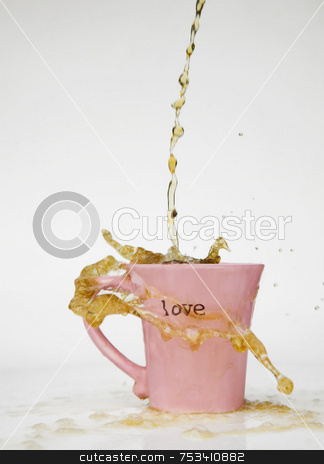Coffee Splash Love Mug stock photo, Coffee splashes over the rim of a pink cup with the word