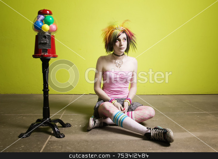 Punk Girl in front of a Green Wall stock photo, Colorful young punk girl sitting in front of a green wall by Scott Griessel
