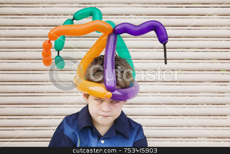 Mad Boy with a Balloon Hat stock photo, Young boy wearing a balloon hat with an angry face by Scott Griessel
