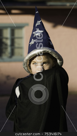 Boy Wizard stock photo, Youn boy with a wizard hiding his face in front of a pink house by Scott Griessel