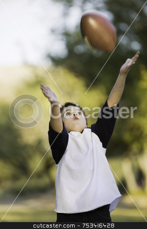Boy catching a football stock photo, Young boy with arms stretched out to catch a football by Scott Griessel