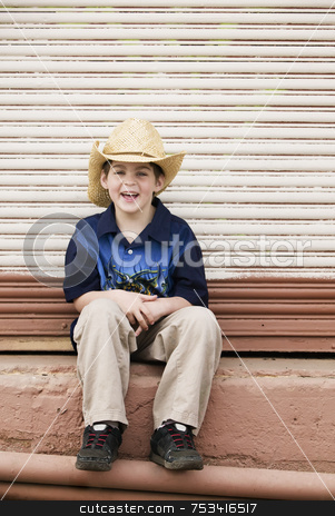 Smiling Boy Wearing a Cowboy hat stock photo, Young Boy in a Straw Cowboy Hat Smiling Broadly by Scott Griessel