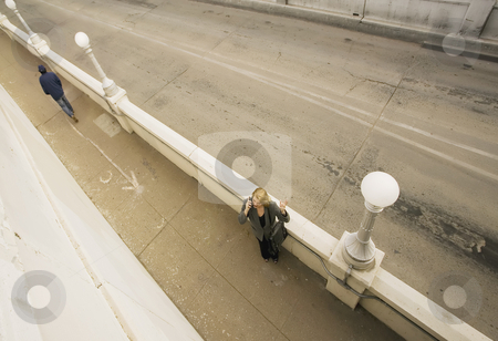 Looking Down on a Woman on Her Cell Phone stock photo, Wide shot from above of  woman on her cell phone next to an empty road. by Scott Griessel