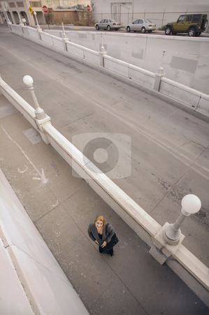Looking Down at a Woman on the Sidwalk stock photo, Wide shot from above of woman on a sidewalk by Scott Griessel