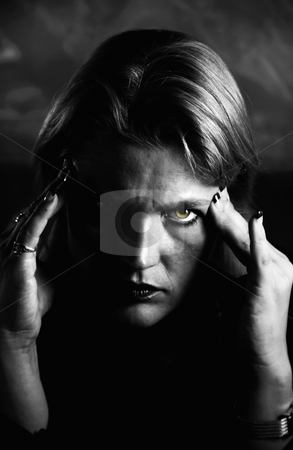 Blonde Woman Touching Forehead stock photo, Close up of blonde woman in a studio setting touching her temples. by Scott Griessel