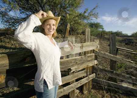 Western Woman stock photo, Western woman leans against a decrepit old split rail fence. by Scott Griessel