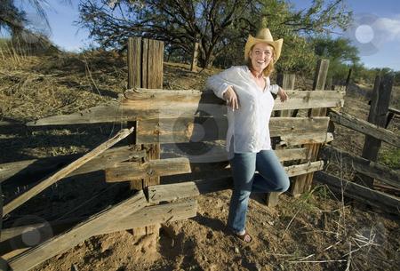 Western Woman stock photo, Western woman leans against a decrepit old split rail fence. by Scott Griessel