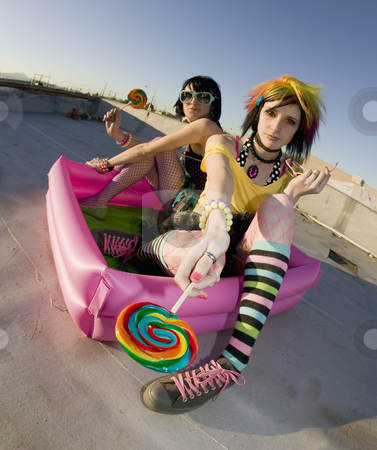 Girsl on a roof in a plastic pool stock photo, Fisheye shot of girls in brightly colored clothing in a plastic pool on a roof with lollipops by Scott Griessel