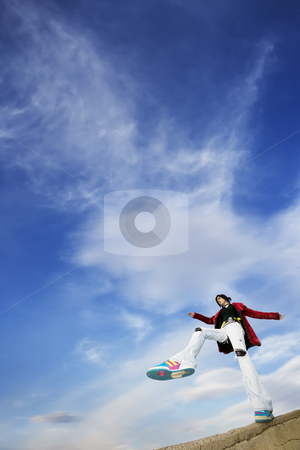 Woman Stepping Against the Sky stock photo, Wide angle shot of woman taking a big step against a cloudy sky by Scott Griessel