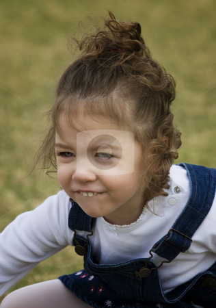 Smiling Girl stock photo, Young girl on grass with a funny smile. by Scott Griessel