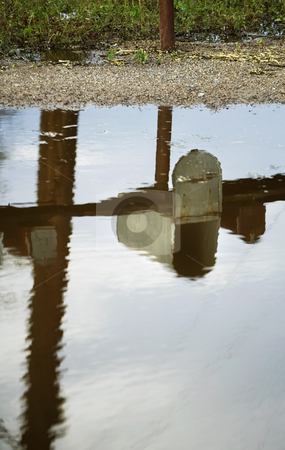 Mailbox Reflected in Puddle stock photo, Open rural mailbox reflected in a puddle after a rain storm. by Scott Griessel