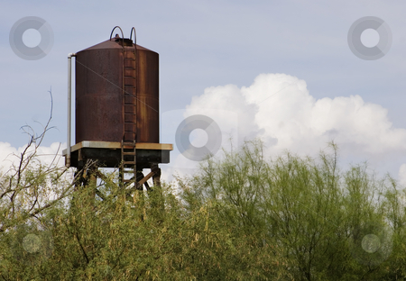Rusty Water Tower stock photo, Rusty water tower with a storm cloud in the background. by Scott Griessel