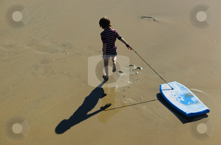 Boy on the Beach stock photo, Young boy on the beach with a small surf board. by Scott Griessel